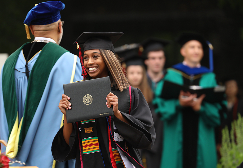 Grad celebrates with diploma