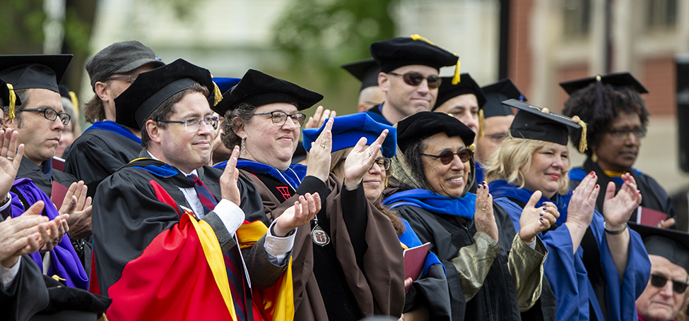Faculty standing and clapping at commencement