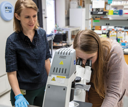 Lilliana Radoshevich looks on while Madeleine Vessely peers through a microscope