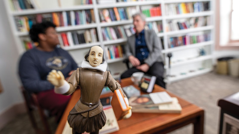 Shakespeare doll with Mellon fellow Elijah Griffin sharing his research with professor John Garrison in background