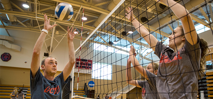 Eric Ragan sets a volleyball on the left side of the net to two women on the other side