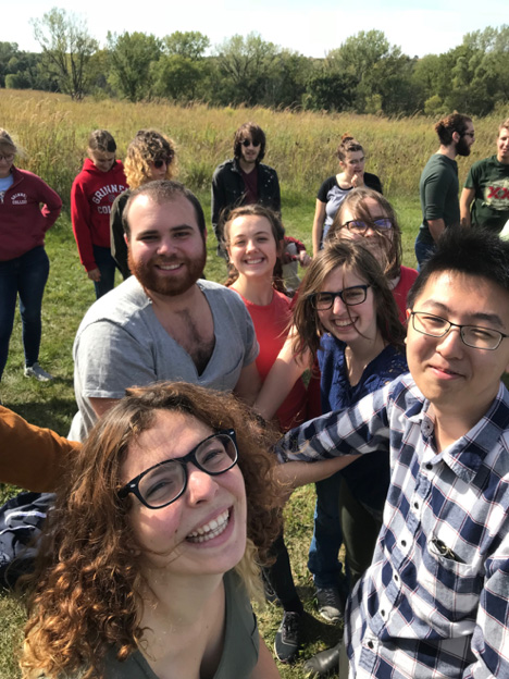 7 Grinnell Singers members stand in the background next to prairie grasses as 6 singers look joyously into the camera, appearing to be doing a team hand stack.
