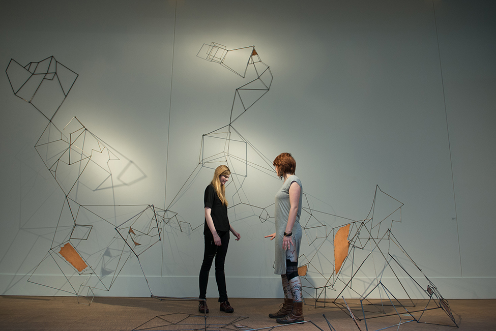 Two students admiring wire art sculpture