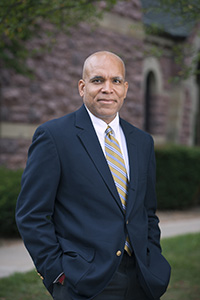 President Raynard S. Kington standing in front of Goodnow Hall