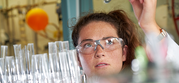 Lucy Chechik, wearing safety glasses, examines a test tube