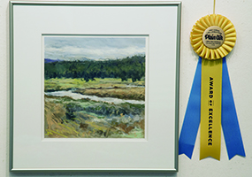 en plein air framed art next to ribbon