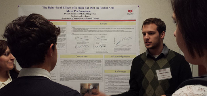 A student explains the results of his neuroscience research project to several conference participants.