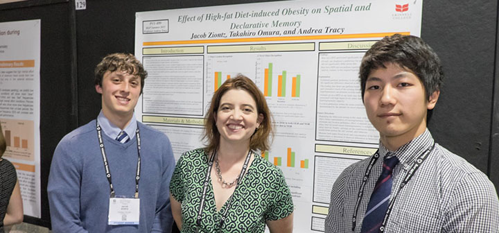 Two students and their research mentor stand in front of their research poster.