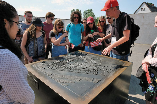 Students at the Sachsenhausen concentration camp memorial look at a model of the camp.