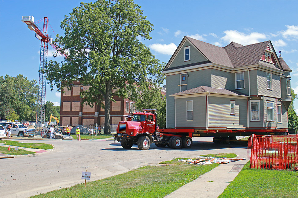 Two-story house on the back of a flat-bed truck that's turning the corner onto Park Street, looking southeast at ARH