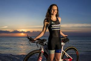 Madeleine Pesch '16 standing on beach with bike
