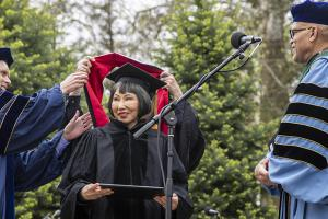 Amy Tan being hooded
