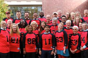 Alumni Council members pose in old Grinnell sports jerseys