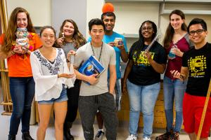 8 students show off items found during the Grinnell Science Project scavenger hung