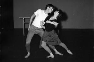 Black and white photo of two dancers, the woman in front, facing the man, with one leg stretched behind her. They are clasping hands