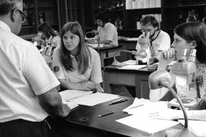 Black and white photo shows students working at desk with manual microscopes, some takling to a professor