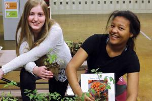 Two students with plants grown in greenhouse