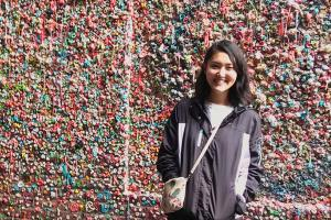 Michi Soderberg '21 stands in front of bubble gum wall