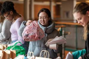 Students choosing from a long, crowded table of packages and one student holding her choice which is wrapped in pink