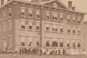 Students stand outside of campus building in 1879