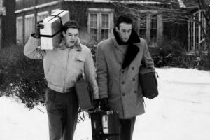 2 students walking in the snow with their laundry