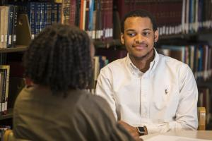 Jovan Johnson talks with student in library