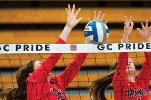 Two players reach for the volleyball behind net printed with GC PRIDE and Honor G