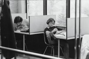 black and white photo of students in small chairs at desks with short barriers to the front