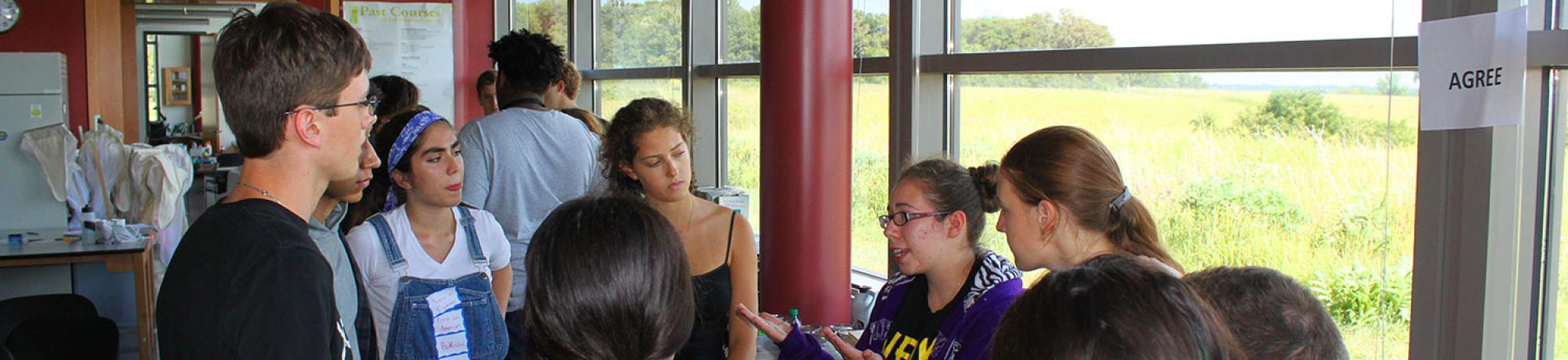 A group of students share in a talking circle. Behind them are windows toward the Iowa prairie.