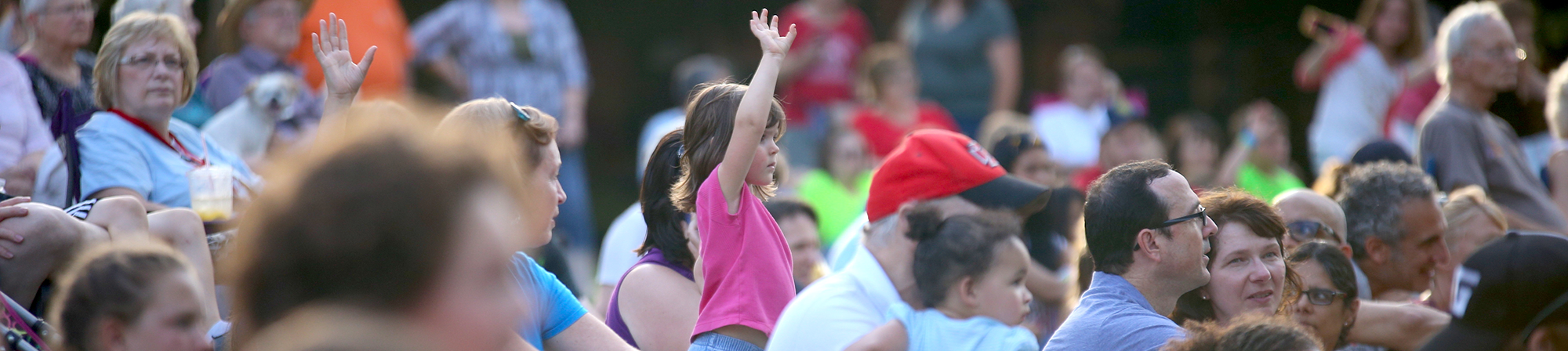 small girl raises hand in the middle of a crowd seated on the lawn