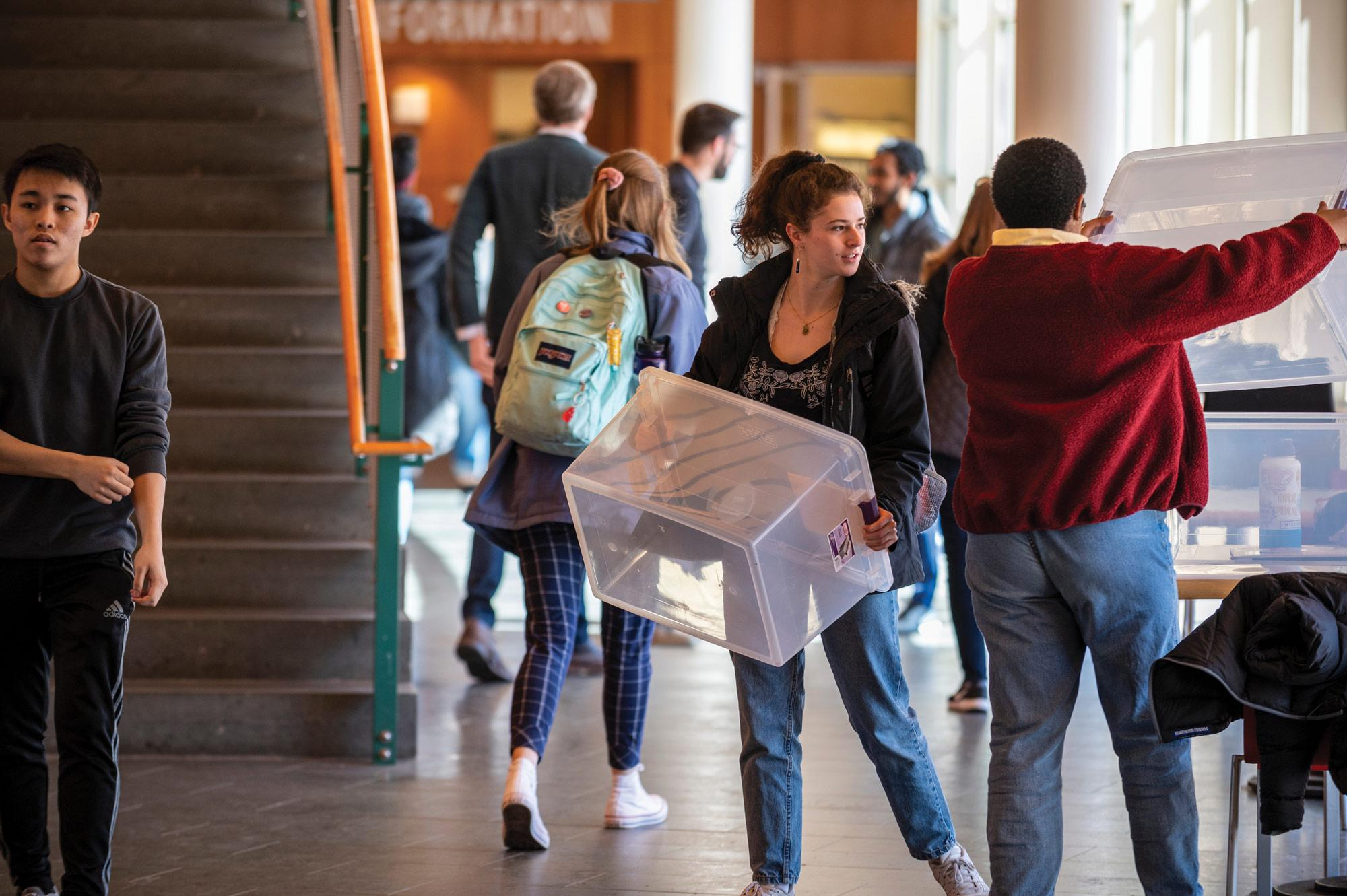 Students pick up totes to pack their belongings before leaving campus.