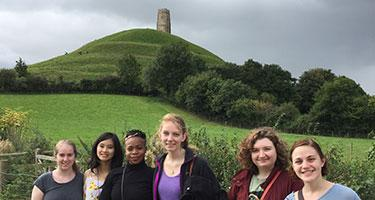 Grinnell-in-London students on field trip in countryside, with old tower in the background