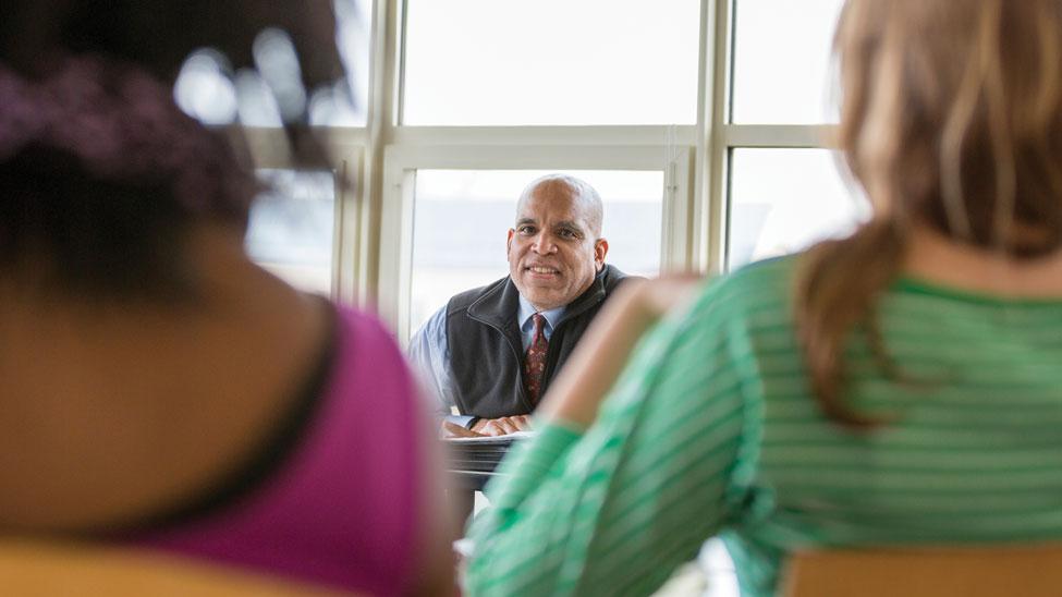 Raynard S. Kington at table in classroom
