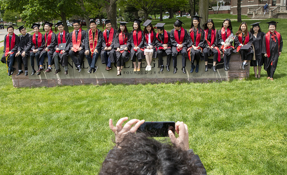 students sitting on the Grinnell College sign