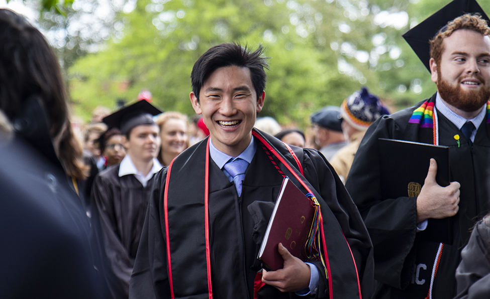 student carrying his diploma