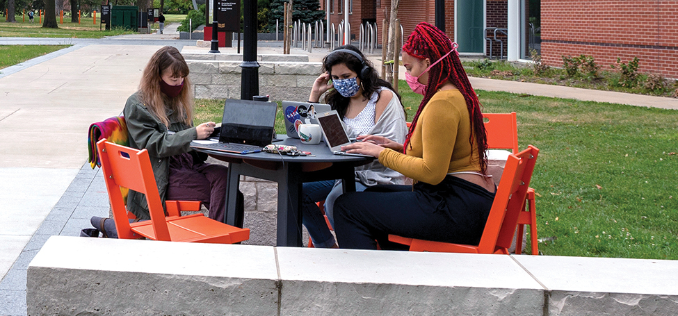 Students in PPE sitting around an outdoor table with their laptops