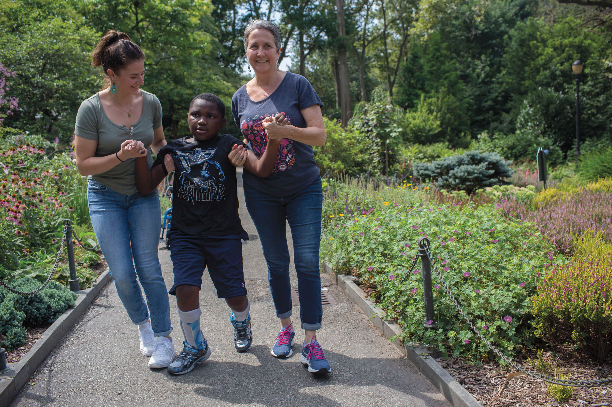 Sarah Weltz, Sandra Joy Stein, and Stein's son walking down a garden path