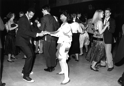 Students in suits and gowns dancing