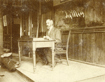 Jesse Macy seated at a desk in the front of a lecture room
