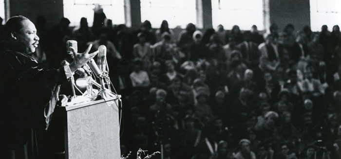 Martin Luther King Jr. preacing from a podium in Darby Gymnasium in front of a packed crowd
