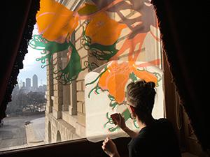 Lee Emma Running installing artwork on window