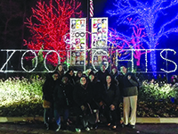 Image of group in front of zoo lights