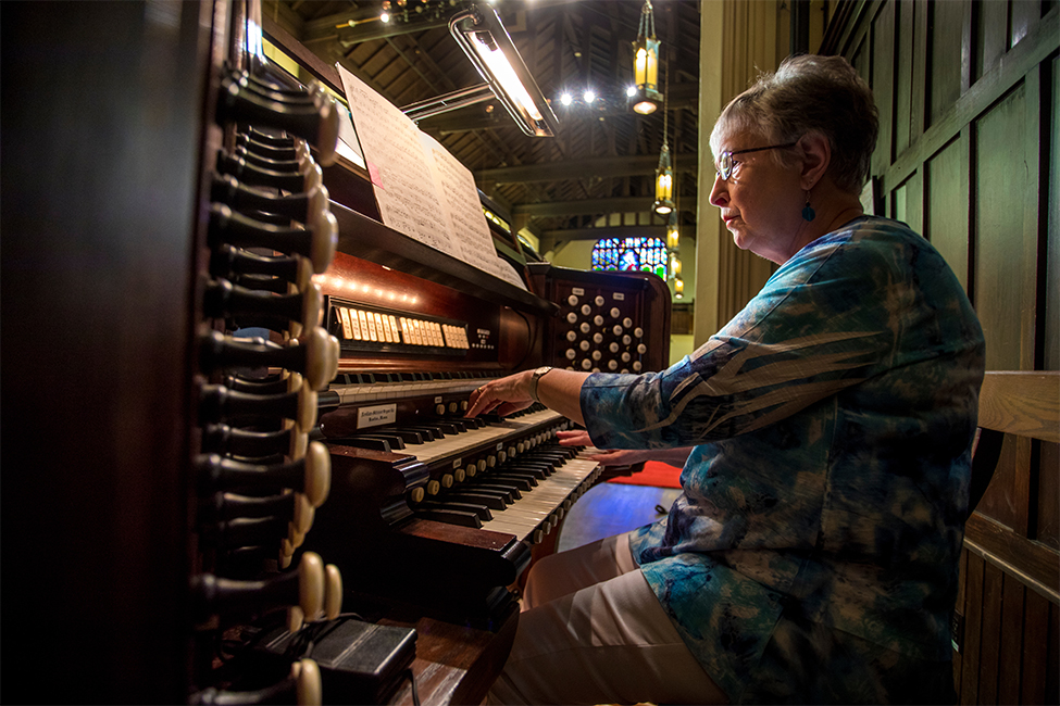 Linda Bryant sitting at the organ in Herrick Chapel