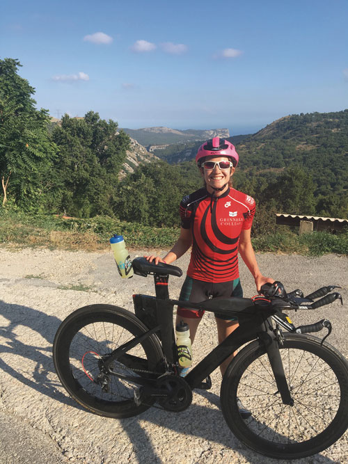 Maddy Pesch in Grinnell riding gear with her bike on a mountain pass
