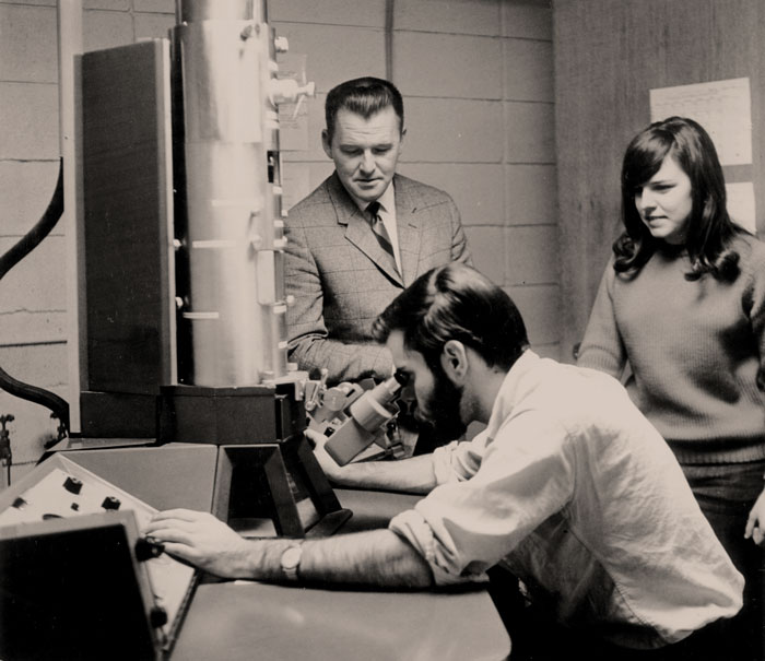 Walker with students in a biology lab with one student using the electron microscope