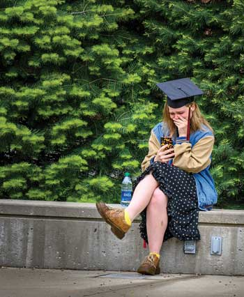 A student wearing her mortar board cap watched her virtual Commencement on campus at the empty stage.