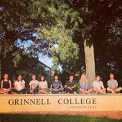 Group of friends by the Grinnell College sign on Park street