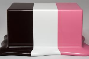 A glossy rectangular box with three stripes of color - brown, cream, and pink - that puddle at the base