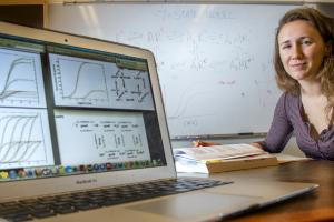 Josie Bircher sits at a laptop and shows data models on a display screen