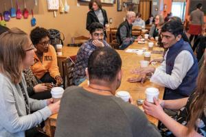 Shafiq R. Kahn talking with Grinnellians around a table
